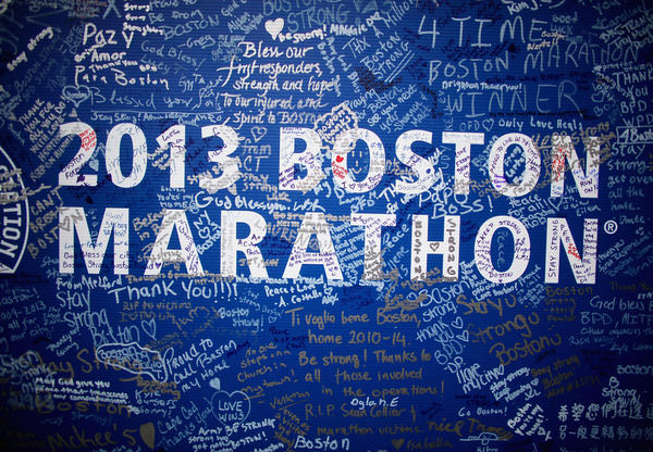 Signatures adorn a Boston Marathon poster near the site of the bombings on Boylston Street. The street fully reopened Wednesday.