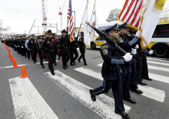 Members of a police honor guard lead a column of law e