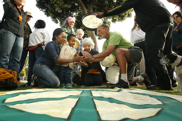 Shay White, left, and her son Elias Washington, join with activist Jerry Rubin, right, and wife Marissa to light a peace candle during an Earth Day ceremony at the Children's Tree of Life at Santa Monica Palisades Park.