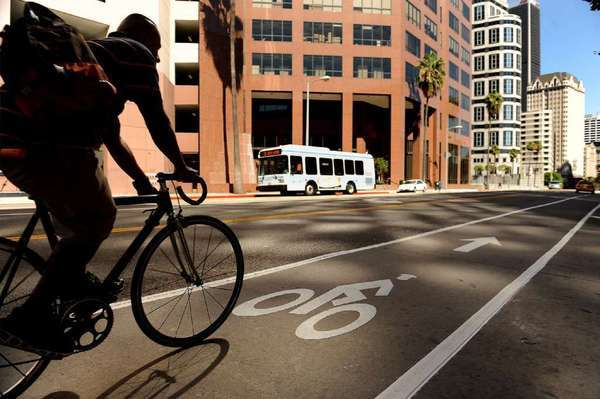 A bicyclist rolls along the bike lane on 7th Street in downtown Los Angeles. The Automobile Club of Southern California reminds bikers to ride in the direction of traffic, not facing it.