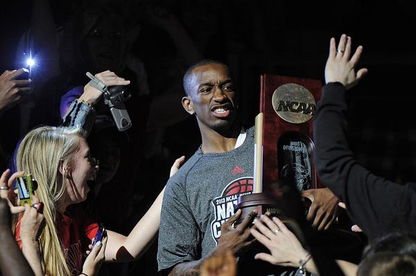 Louisville Cardinals guard Russ Smith carries the NCAA Midwest Regional trophy through the crowd at the KFC YUM! Center during their celebration for winning the NCAA title.