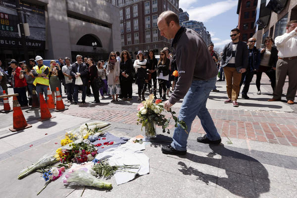 David Robbins of Needham, Mass., places flowers at the site where the first bomb detonated April 15 near the finish line of the Boston Marathon on Boylston Street.