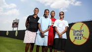 Jamani Ridley, 2nd from left, is shown with her mother, Jocelyn, left; brother, Josias; and sister, Jamari. Jamani, who is blind and has a condition that has resulted in 6 heart attacks, cheers on Jamari and the rest of Pine Castle Christian's softball team. (Jacob Langston, Orlando Sentinel)