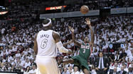 Milwaukee Bucks guard Brandon Jennings goes to the floor after being fouled by Miami Heat defender Norris Cole as the Heat's LeBron James looks on in Miami