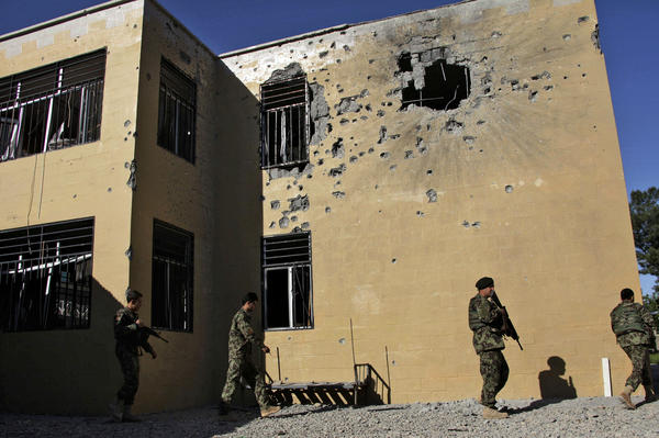 Afghan soldiers patrol outside the destroyed courthouse in Farah, in western Afghanistan. The Taliban has declared courthouses and their personnel targets.