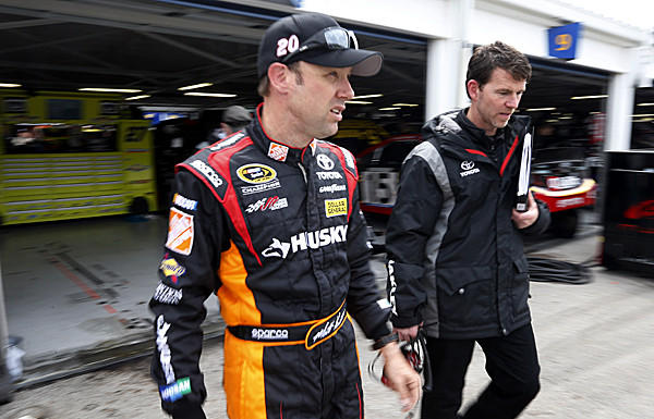 Matt Kenseth, left, walks from the garage following practice for the NASCAR Sprint Cup race at Kansas Speedway.