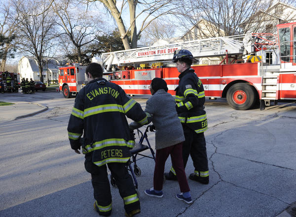 Evanston firefighters help a homeowner whose home was damaged in a house fire on the 1900 block of Hartrey in Evanston.