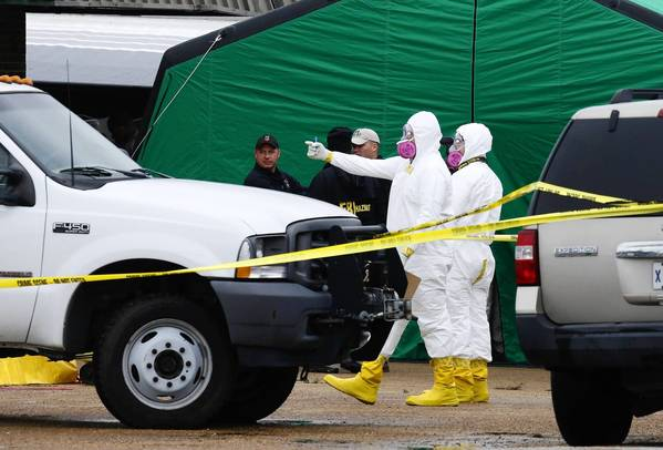 Federal investigators in protective suits gather outside a Tupelo, Miss., business space where James Everett Dutschke is said to have operated a martial arts studio. Authorities are investigating the site in connection with the ricin case, but Dutschke has not been arrested or charged.