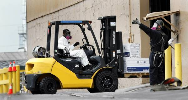 Wearing breathing devices, employees move boxes around by forklift at the lead smelting company Exide Technologies in Vernon. State regulators took the highly unusual step Wednesday of suspending operations at the battery recycler.