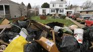 Three generations worth of ruined possessions were piled alongside mounds of damp drywall and sodden insulation on the front lawn of Kristen Scelonge's house, most of it waiting to be loaded into a dumpster.