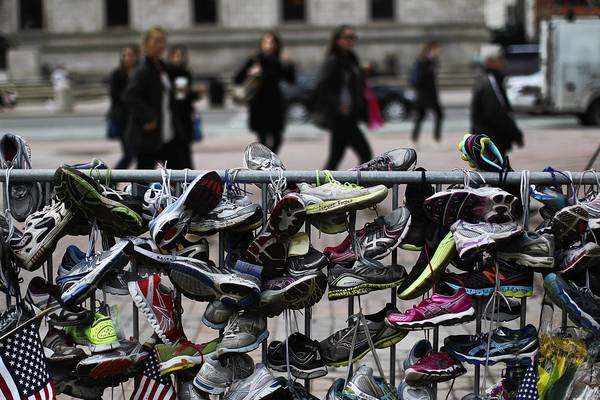 Running shoes hanging from a fence in Boston's Copley Square on Wednesday pay tribute to those affected by the Boston Marathon bombings.