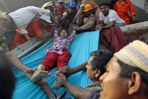 Rescuers lower a survivor from debris of a building that collapsed in Bangladesh.