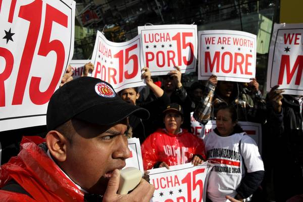 "Victor Guzman, a McDonald's worker at the Clark and Lake location for one year, leads the ""Fight for 15"" rally and march in front of the Rock 'n' Roll McDonald's, farther north in Chicago, on Wednesday."
