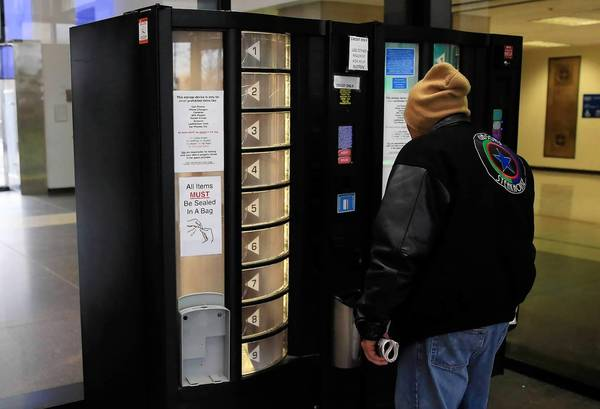 A man stores his cellphone for $3 in a vending machine at the Leighton Criminal Court Building in Chicago.