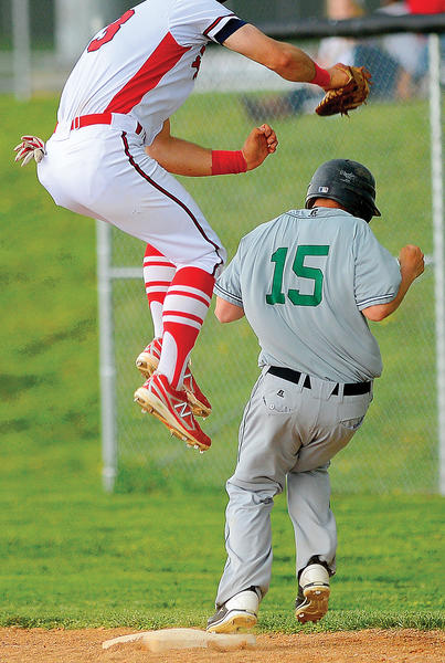 South Hagerstown runner Chase Eichelberger (15) reaches first base safely by ducking under a flying tag attempt by North Hagerstown first baseman Andrew Yacyk.