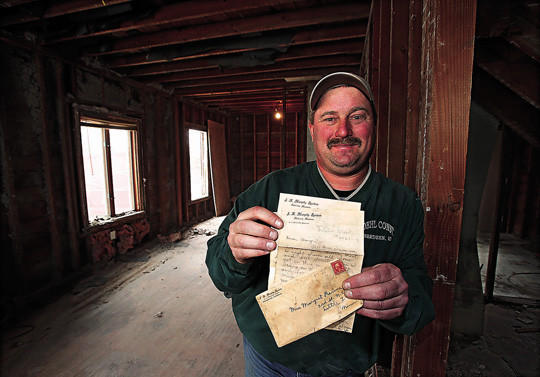 Troy Woehl holds a love letter from 1909 that he found in the first floor ceiling of a home he is remodeling at 917 Fourth Avenue Southwest. photo by john davis taken 4/18/2013