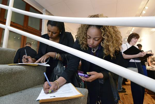 Job seekers Lovesha Johnson, center, and Charlene Sales, left, fill out a job applications at a restaurant job fair in New York.