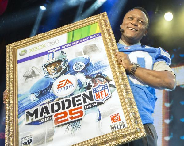 Hall of Fame running back Barry Sanders holds up a mock-up of the Madden 25 video game cover during the EA Sports Madden NFL 25 cover reveal Wednesday on SportsNation in New York City.