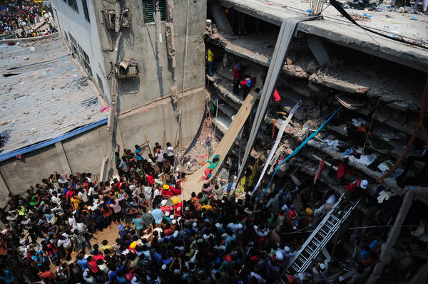 Volunteers use a length of cloth as a slide to move victims recovered from the rubble after a building collapsed on the outskirts of Dhaka, Bangladesh.