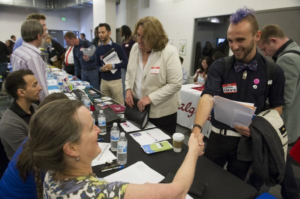 Applicants meet with potential employers at a job fair in San Francisco this week. A new survey shows Americans are feeling better about their job prospects.