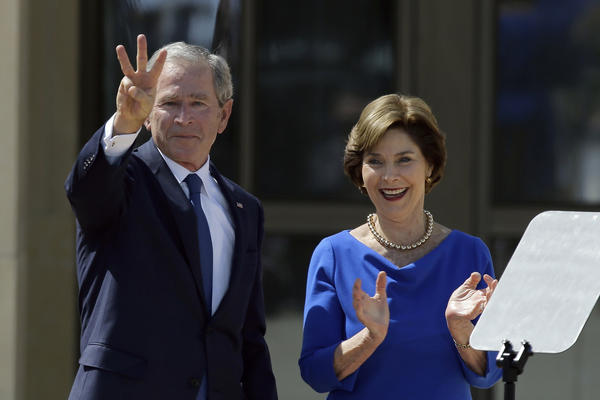 "Former President George W. Bush, accompanied by his wife former first lady Laura Bush, flashes the ""W"" sign after his speech during the dedication of the George W. Bush Presidential Center in Dallas."