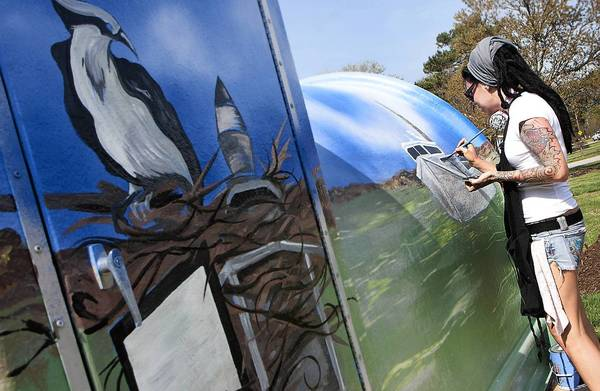 Jessye Abell is painting a watermen-themed mural on a pump station in Poquoson. It is part of the Great American Clean Up