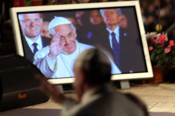 Pope Francis is seen on a screen as he presides over the Way of The Cross procession at the Colosseum on Good Friday in Rome, Italy.