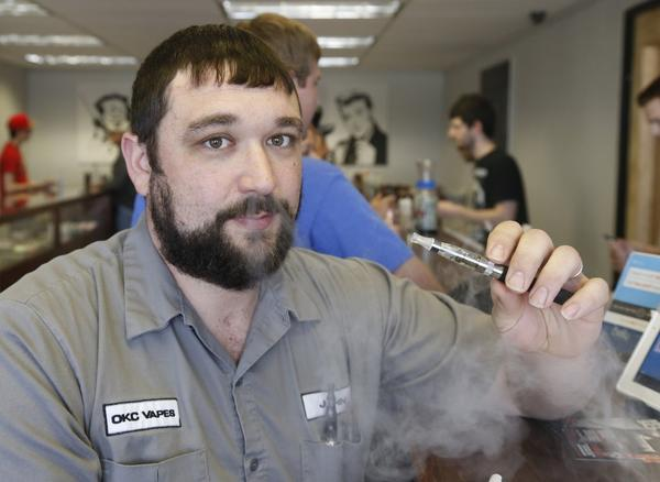 John Durst demonstrates the use of an electronic cigarette at his shop in Oklahoma City. Marlboro maker Altria Group Inc. said Thursday it is rolling out an electronic cigarette.