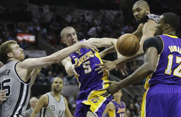 Steve Blake passes to teammate Dwight Howard while being pressured by San Antonio's Matt Bonner, left, and Tim Duncan.