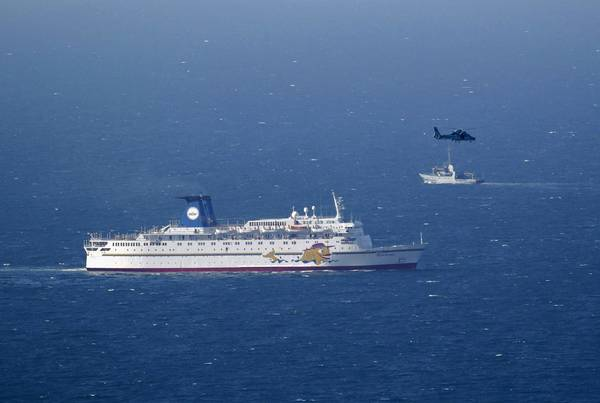 An Israeli military ship, background, and an air force helicopter operate next to a cruise ship off the coast of Haifa. The military said it shot down a drone five miles off the northern coast.