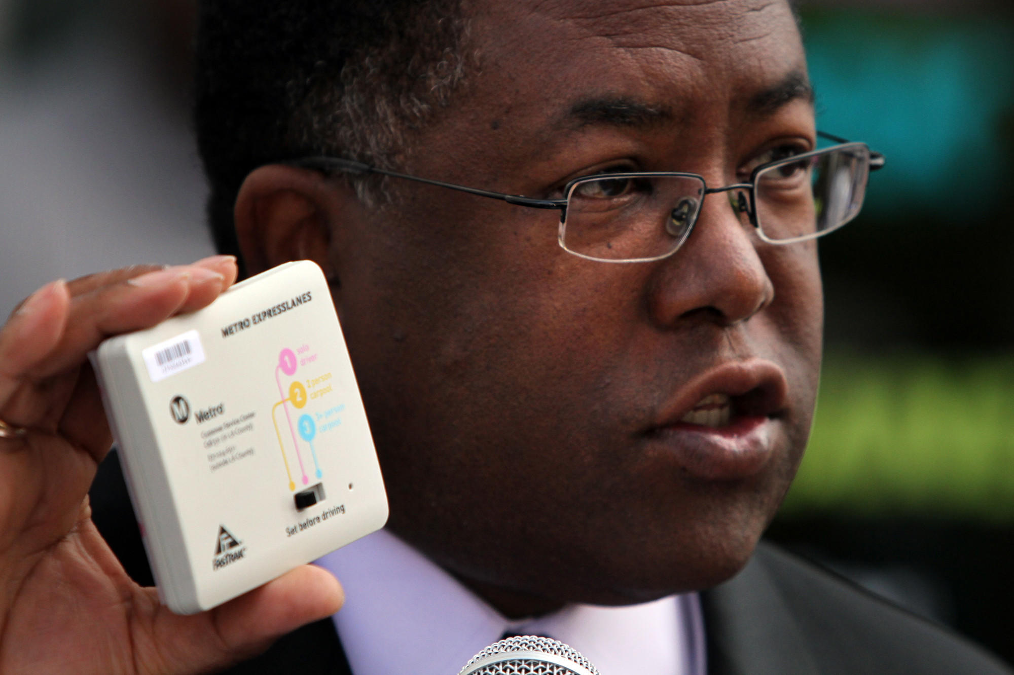 Los Angeles County Supervisor Mark Ridley-Thomas shows a FasTrak device in 2012.