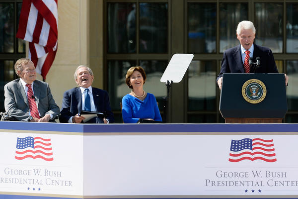 President George W. Bush laughs during President Clinton's speech as President George H.W. Bush and former First Lady Laura Bush look on during the opening ceremony of the George W. Bush Presidential Center in Dallas.