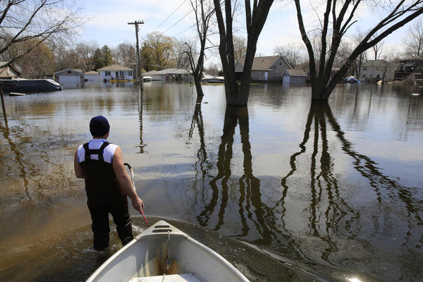 John Annarella, 47, returns a boat Monday to the flooded Fox Lake home of his brother-in-law Dave Marino, whom Annarella was helping pump water from the house on Oak Lane.