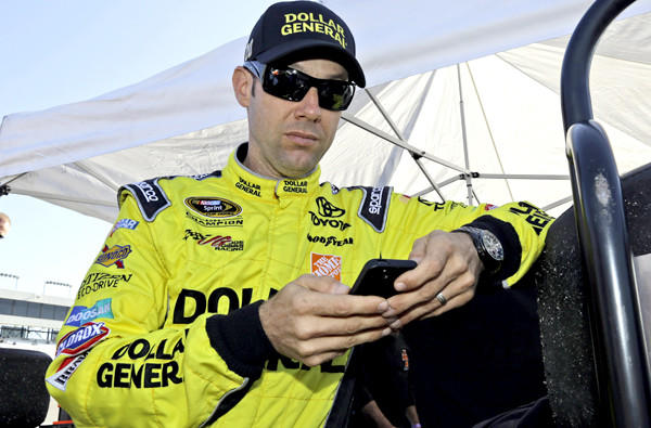 Matt Kenseth checks his phone before practice for Denny Hamlin's Charity Race at Richmond International Raceway on Thursday.