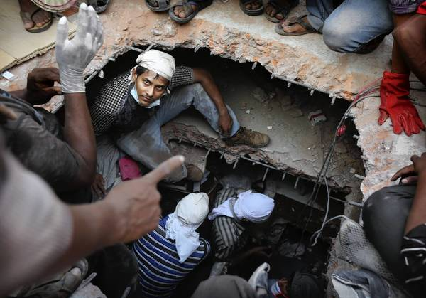 A rescuer looks out from a hole cut in the concrete as he searches for survivors at a collapsed building in Savar, Bangladesh. At least 238 people were killed.