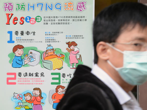 A man walks past an H7N9 poster outside the National Taiwan University Hospital in Taipei.