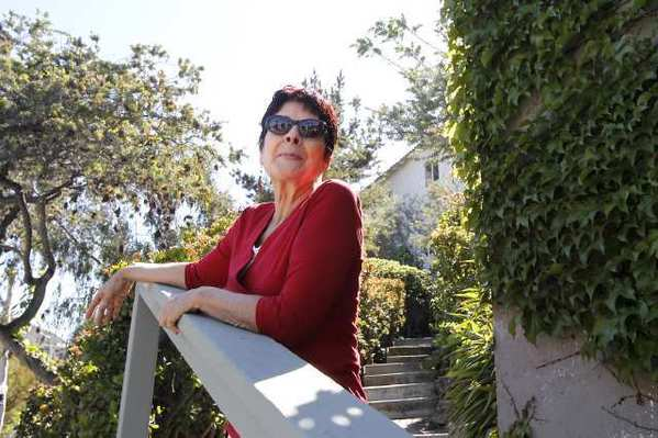 Susana Cruciana stands on the stair path at the home where she grew up on Mermaid Street. Cruciana now finds challenges to stay in the city she loves and calls home.