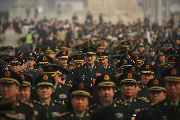 Delegates from Chinese People's Liberation Army march from Tiananmen Square to the Great Hall of the People to attend a plenary session of the National People's Congress during severe pollution in Beijing, China.