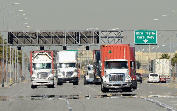 Trucks hauling containers arrive at the Port of Los Angeles.