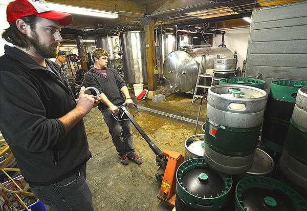 Jesse Rotz, left, watches as his business partner, Ryan Richards, pulls a pallet of chilled beer kegs Thursday in the production area of Roy-Pitz Brewing Co. A pub and restaurant are the latest additions to the five-year-old business.