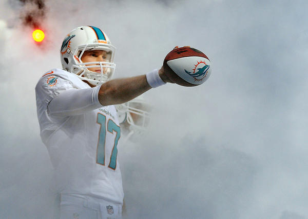 Miami Gardens--- fl-dolphins-uniforms-042513a---Miami Dolphins quarterback Ryan Tannehill comes through the dry ice to unveil the new team uniform at a kick-off part Thursday evening at SunLife Stadium. Robert Duyos, Sun Sentinel