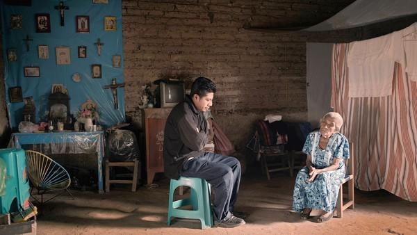 "Pedro (Pedro De los Santos) and his grandmother (Maria Cano Diaz) discuss preparations for her funeral procession in ""Aqui y Alla."""