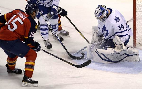 Toronto Maple Leafs' James Reimer (R) makes a save against Florida Panthers Drew Shore (L) during the second period of their NHL hockey game in Sunrise, Florida April 25, 2013. REUTERS/Rhona Wise (UNITED STATES - Tags: SPORT ICE HOCKEY) ORG XMIT: MIA12