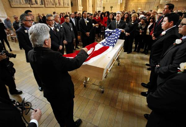 The family of Sal Castro stands around his casket as an American flag is placed on it during his funeral at the Cathedral of Our Lady of the Angels.