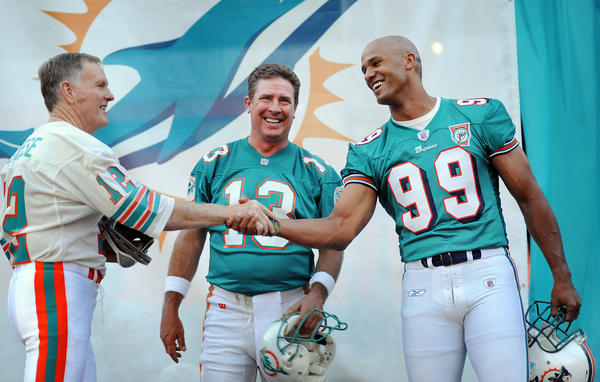 Miami Dolphins legends Bob Griese, Dan Marino, and Jason Taylor share a light moment during the legends segment of the party to unveil the new 2013 Dolphins uniforms Thursday evening at SunLife Stadium.