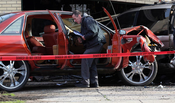 Detectives survey the scene of a car crash on West 116th Street at South Lowe Avenue on Friday. The driver of the sedan was shot two blocks away, then drove away from the scene, only to hit the garage and a parked minivan.