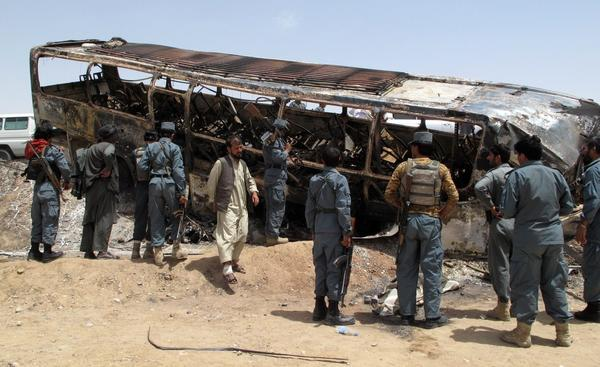 Afghan security officials on Friday survey the scene of a transport accident in Maiwand district of Helman province, Afghanistan.