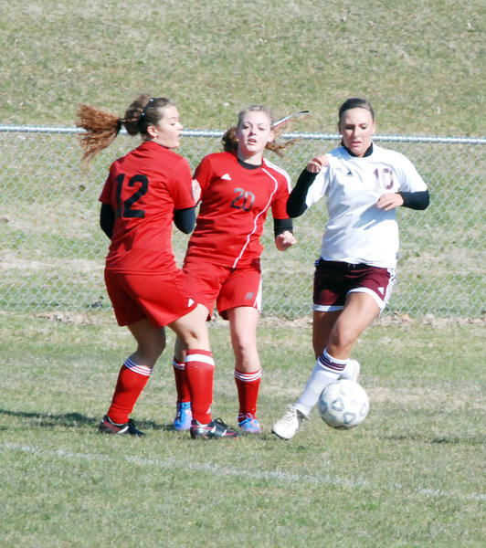 Charlevoix forward Hannah Herboldsheimer (right) weaves through the East Jordan defense of Jessica Peck (left) and Tess McNitt (middle) during a Lake Michigan Conference match on Thursday at Shanahan Field in Charlevoix.