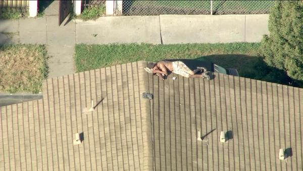 Los Angeles Police have surrounded a home in Venice, where a shirtless burglary suspect is perched on a rooftop.