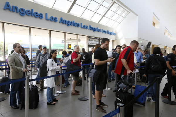 Travelers wait in line at Los Angeles International Airport. The legislation will end furloughs for air-traffic controllers that have caused flight delays at airports nationwide.
